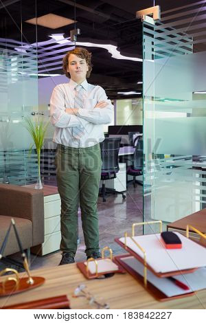 Handsome teenager in shirt and tie poses in modern office with table