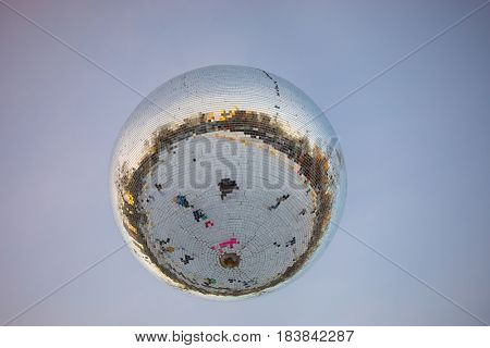 Big mirror ball with reflection of people hanging from ceiling