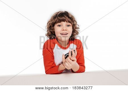 Curly smiling boy holding smarphone in hands