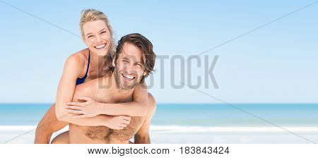 Happy man in love giving piggyback ride to smiling woman at the beach. Couple enjoying vacation at beach with copy space. Banner of summer young couple in a tropical beach