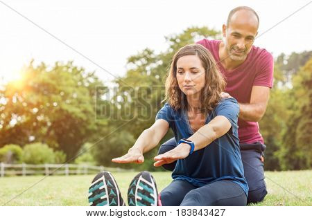 Mature couple doing exercise outdoor on grass. Senior woman with male personal trainer exercising in gym fitness. Woman stretching and touching her tiptoe with the help of her multiethnic boyfriend.