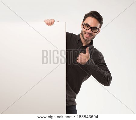 Young happy man portrait of a confident businessman showing presentation, pointing paper placard gray background. Ideal for banners, registration forms, presentation, landings, presenting concept