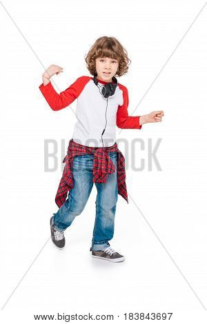 Cute boy in headphone dancing isolated in white