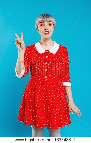 Close up portrait beautiful dollish girl with short light violet hair wearing red dress showing victory gesture over blue background. Copy space.