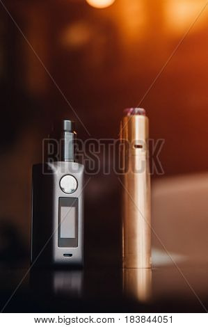 Vaping set on wooden table. mod. steam. vape