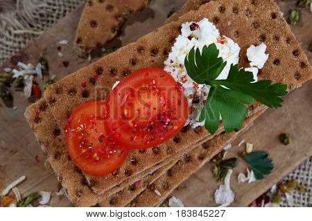 Bread with cottage cheese and cherry tomatoes on wooden table