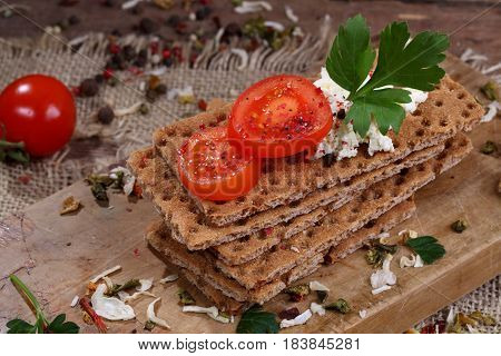 Rye bread with cottage cheese and cherry tomatoes on wooden table
