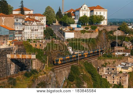 PORTO, PORTUGAL - APR 16, 2017: Train of Porto Metro in Old Town. The network has 6 lines and reaches seven municipalities within the metropolitan Porto area.