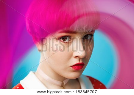 Close up artistic conceptual portrait of beautiful dollish girl with short light violet hair wearing red dress over blue background. Blurry forefront. Copy space.