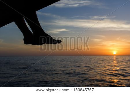 Photo of scarlet sunset on beach with seated man on beach