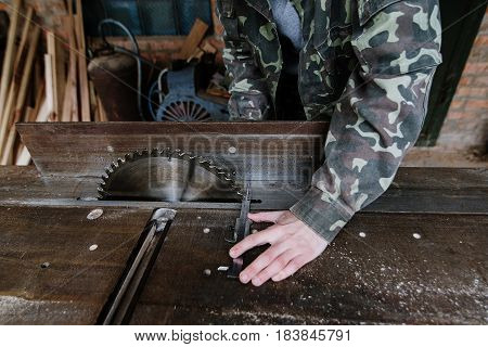 Carpenter measures the width of the board with a calipers in the workplace. Circular saw. Carpenter tool