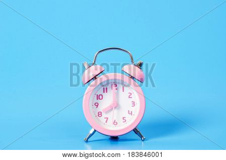 Vintage pink alarm clock on blue background with copy space.