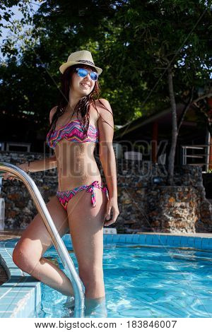 Slender woman on stairs of pool in summer