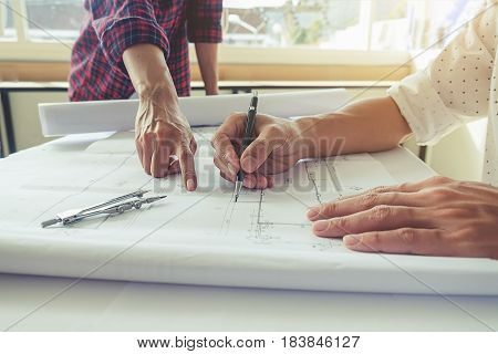 Hands of Engineer working on blueprint. Construction concept. Engineering tools.Vintage tone retro filter effect. soft focus(selective focus)