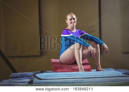 Portrait of a female gymnast sitting on big wedge in the gymnasium