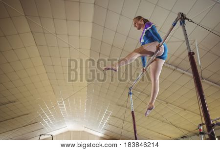 Female gymnast practicing gymnastics on the horizontal bar in the gymnasium