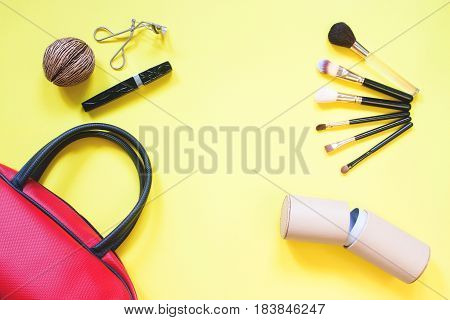 Face make up set and bag flat lay on yellow background