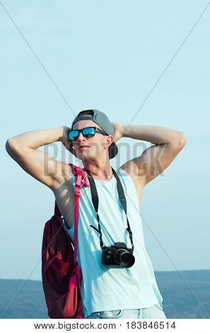 Young man caucasian traveler or photographer with muscular hands triceps biceps in stylish sunglasses and cap camera red backpack enjoy on sunny day on blue sky. Leisure and summer vacation