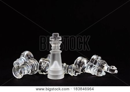 chess of glass. The figure of the king standing over the defeated opponent's pieces on a black background. Business metaphor.