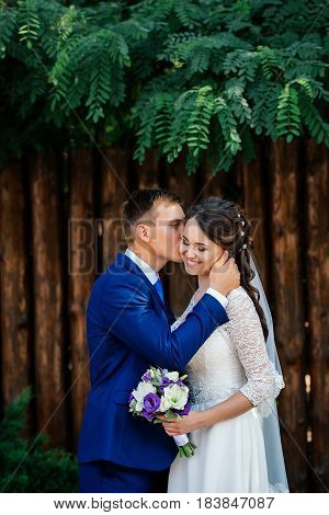 Groom embraces and kisses the bride. Bride and groom near the wooden wall from logs in the park. Wedding couple in love at wedding day