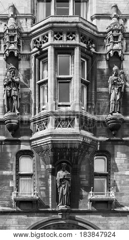 Architectural exterior detail of gatehouse of Gonville and Caius College located in the Senate House Passage in Cambridge University. Cambridge United Kingdom. Black and white.