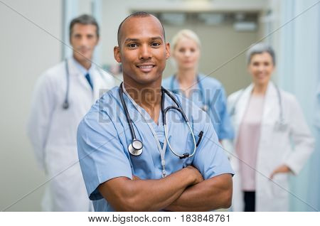 Confident male nurse in front of his medical team looking at camera. Smiling african young surgeon standing in front of his colleagues with folded arms. Multiethnic doctor with staff in background.