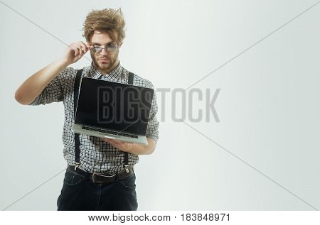 Serious man or student businessman with beard and stylish hair in nerd glasses with laptop computer in checkered shirt with suspenders on white background. Education and technology copy space