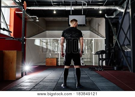 Young man preparing muscles before training back view . Muscular athlete exercising. Workout lifestyle concept. Full body length portrait