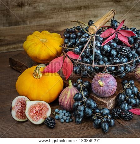 Beautiful autumn still life: black grapes in a basket on the old cutting board as well as ripe figs red raspberries orange pumpkin and blackberries with autumn leaves on the wooden background