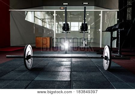 Barbell on floor in the dark gym