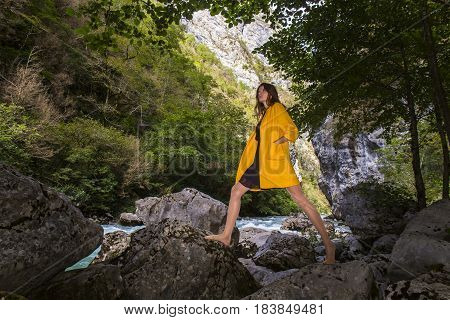 Young beautiful long hair woman stepping by the rocks on mountain river background