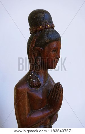 Wooden statue of female with thai culture greeting abstract on white background