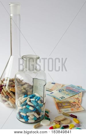 The medical pills are on a money. Colorful pills and money on a white background.