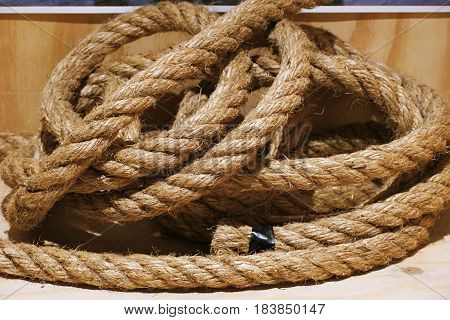 Rolled brown rope knot isolated on wooden background