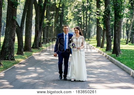 The bride and groom walking down the stairs in the park. The bridegroom embraces the bride. Wedding couple in love at wedding day