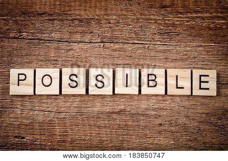 The word Possible spelled with wood blocks on old wooden backgroun