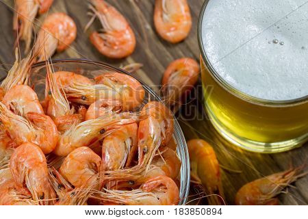 Boiled shrimps in a glass bowl and beer in a glass top veiw, close-up