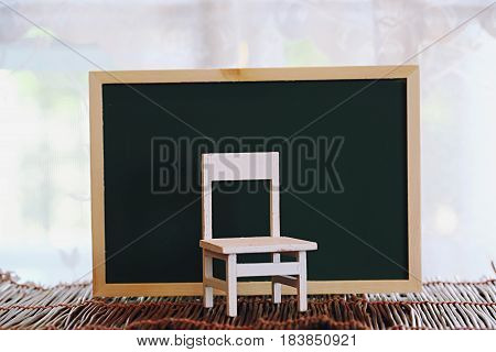 White chair with green board wooden decoration on blur window background