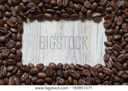 Roasted coffee beans around square space of wood, top view
