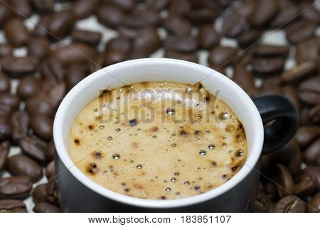 Cup of fresh coffee on background with roasted cofee beans, close-up