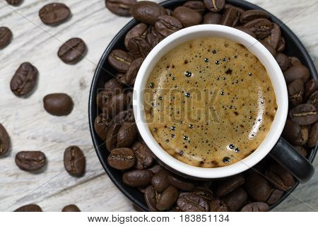 Cup of black coffee in a bowl with cofee beans on wooden background, top view, close-up