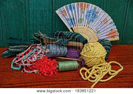 A set of multi-colored threads, a woolen ball and a fan on the table