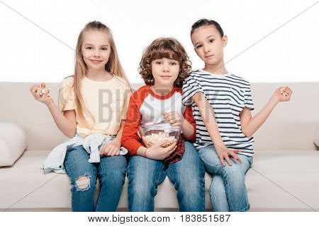 Cheerful friends sitting on couch with popcorn
