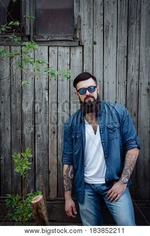 Portrait of a serious brutal stylish bearded man with tattoo in jeans shirt outdoors. Woodden background