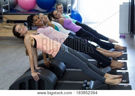 Portrait of smiling fit women exercising on arc barrel in gym