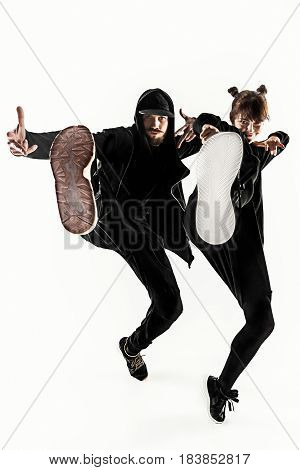The silhouettes of two young hip hop male and female break dancers dancing on white studio background