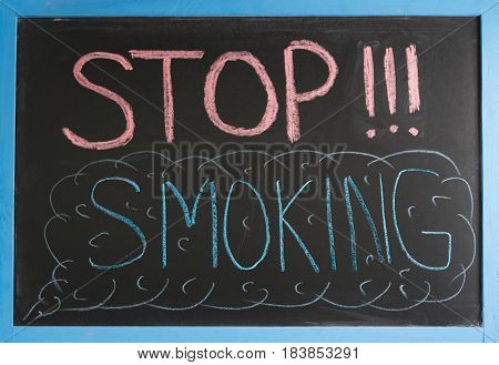 The inscription of stop smoking chalk on a slate in a blue frame