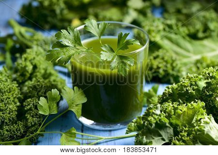 a glass with kale smoothie topped with a twig of parsley and some leaves of kale on a blue rustic wooden table