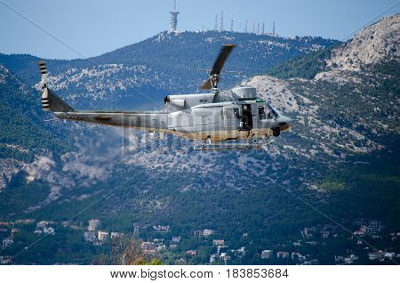 Helicopter bell uh 1.Exhaust gases machine gunner sidebackground mountain antennas