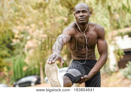 Fit shirtless young black man doing stretching before running in urban park. Young male exercising with naked torso listening to music with headphones.